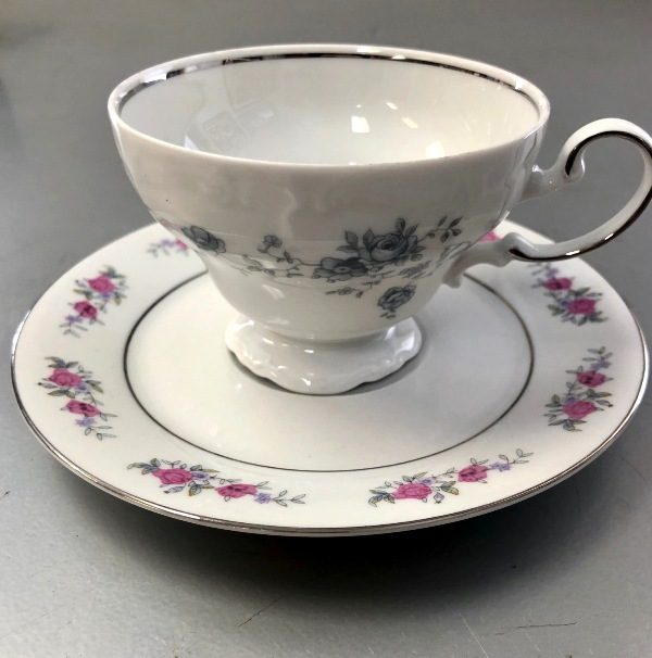 antique tea cup sitting on top of an antique plate with a pink floral pattern